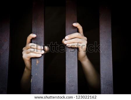 prisoner grasp cage bars - stock photo