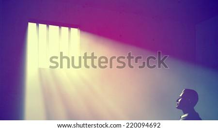 prisoner in dark room with light beams - stock photo