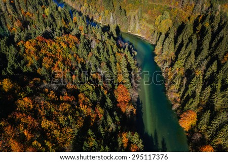 Pristine alpine turquoise river meandering through forested landscape in a sunny autumn day, aerial view. Pristine, clean nature, pure water, environment concept.  - stock photo