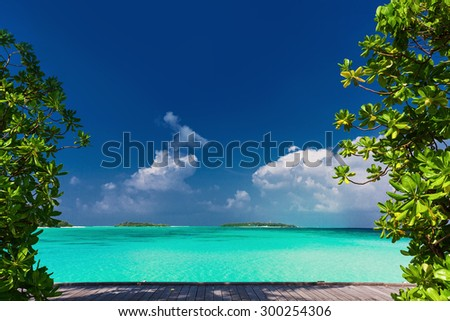 Pristine beach on tropical island during sunny day framed by green trees - stock photo
