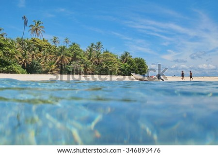 Pristine Caribbean island with tropical vegetation and a boat on the beach with tourists, viewed from sea surface, Panama - stock photo