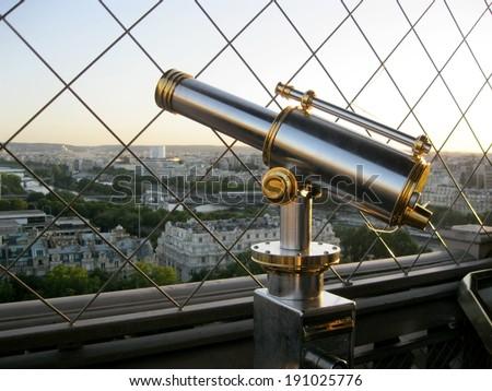 Pristine telescope on the Eiffel Tower overlooking Paris - stock photo