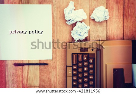 Privacy policy message on a white background against view of an old typewriter and paper - stock photo