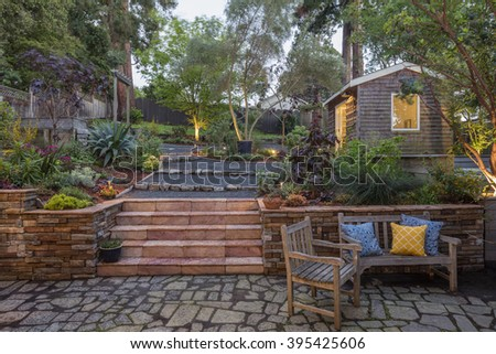 Private beautiful hillside Garden with, selected stone staircase, wooden bench, pillows and chair.   - stock photo