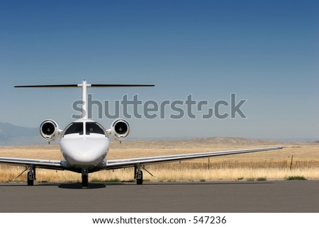 private business jet parked at the airport with copyspace - stock photo
