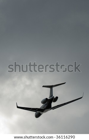 private business jet taking off into a stormy gray sky - stock photo