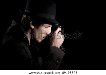 Private detective taking pictures with a small camera, isolated in black