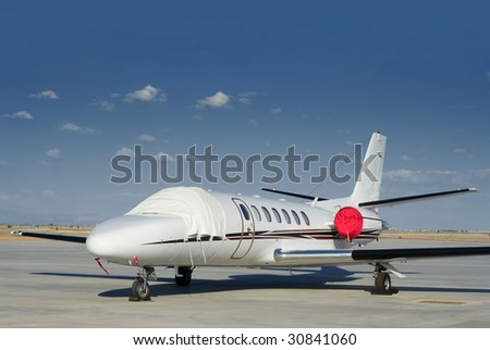 Private exclusive small jet aircraft parked on tarmac of airport.  Blue sky area for copy text - stock photo