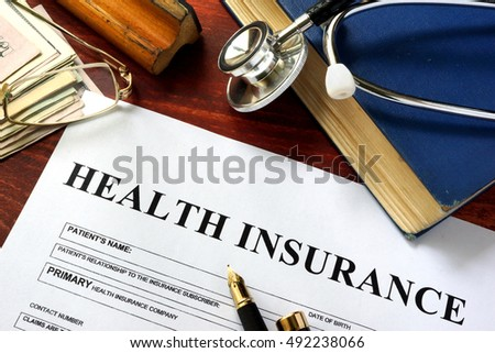 Private health insurance on a wooden surface with glasses.