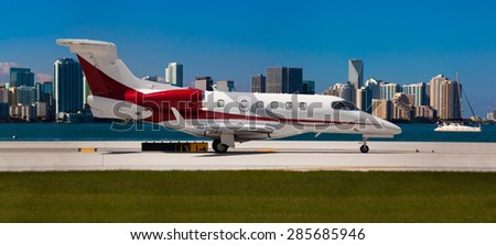 Private jet on the runway with city in the background  - stock photo
