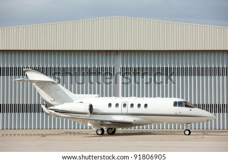 Private jet parked in front of hangar - stock photo