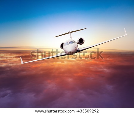 Private jet plane flying above clouds in beautiful sunset. Shot from front view - stock photo