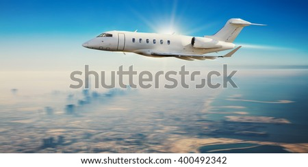 Private jet plane flying over modern city