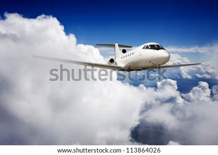 Private jet plane in the blue sky. - stock photo