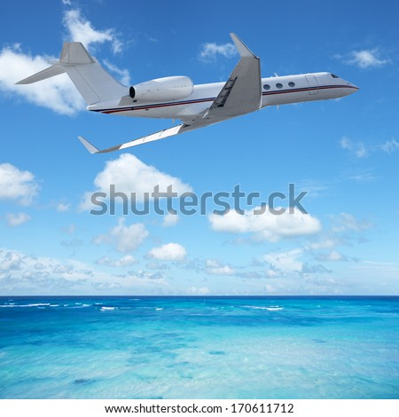 Private jet plane over the tropical sea - stock photo