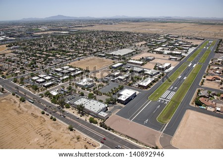 Private owned, public use airport in Chandler, Arizona with a mix of industrial and residential structures accessible by aircraft - stock photo