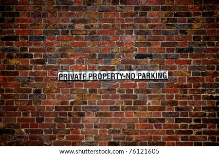 PRIVATE PROPERTY - NO PARKING  sign on very old brick wall - Hampton Court, London, UK - stock photo