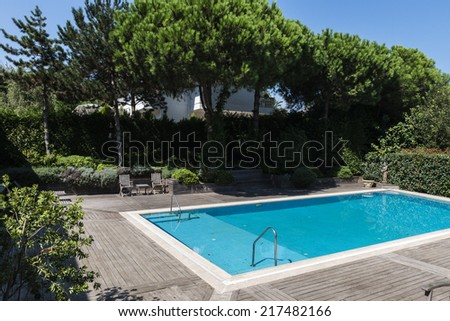 Private swimming pool in garden  - stock photo