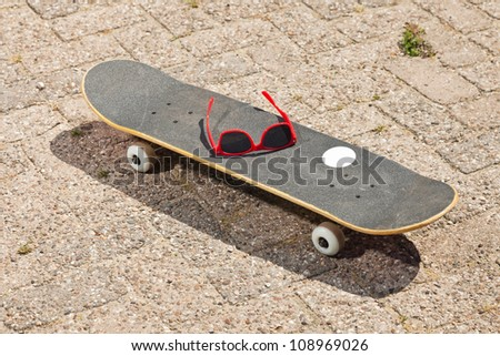 Pro skateboard with red sunglasses on it on the street. - stock photo