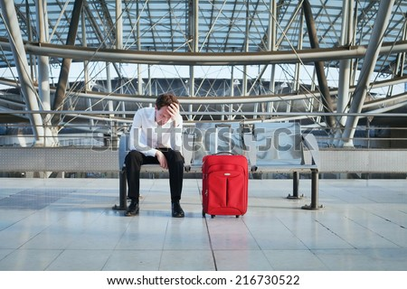 problem in the airport, tired man waiting in the terminal with luggage - stock photo