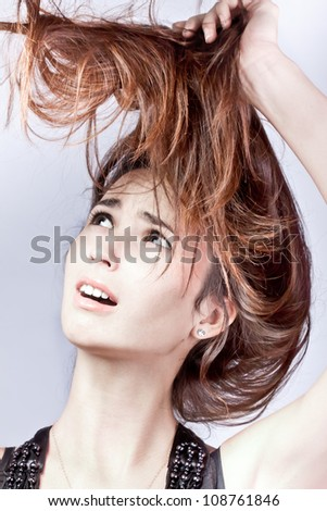 Problem with hair. Woman worriedly looks at the tangled hair, she is dissatisfied with their condition