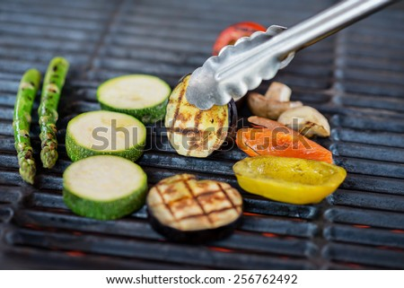 process of cooking vegetables on the grill - chef puts on a grill grate mix of tomatoes, asparagus, zucchini, bell peppers and mushrooms - stock photo