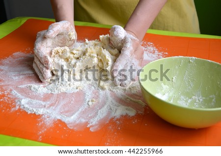 Process of making a dough from farina and butter on orange silicone pad - stock photo