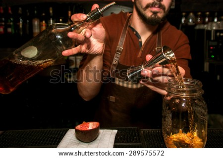 process of preparing a cocktail bartender's from passion fruits  - stock photo