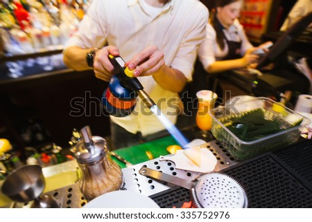 process of preparing a cocktail. Bartender sends fire on a lemon - stock photo