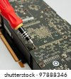 Process of repairing computer electronic board; closeup of video card and screwdriver - stock photo