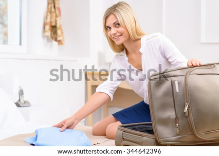 Process of unpacking. Young appealing lady is busy unpacking her large suitcase.  - stock photo