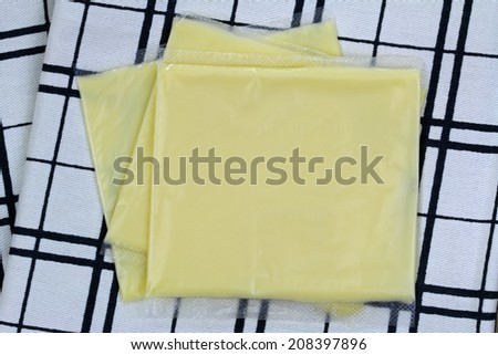 Processed Cheddar Cheese in individual wrapped slides, on a checked cloth - stock photo