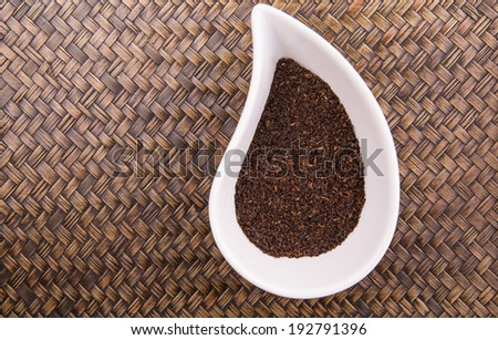 Processed dried tea leaves  a white ceramic container over wicker background