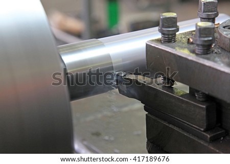 Processing of steel parts with a chisel on a lathe - stock photo