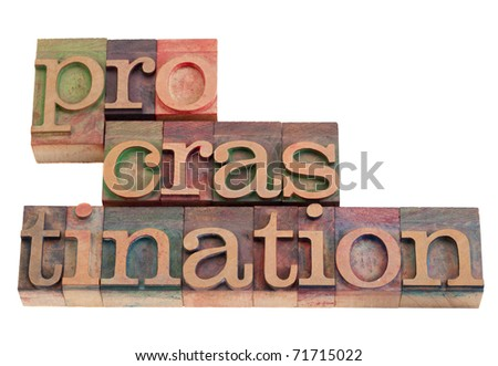 procrastination word abstract in vintage wooden letterpress printing blocks, stained by color inks, isolated on white