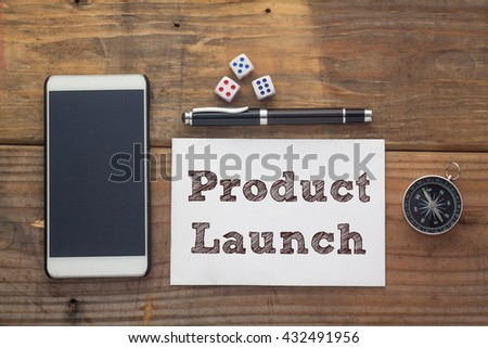 Product Launch Words written on white on wooden desk with dice,compass,smart phone and pen.Top view conceptual - stock photo