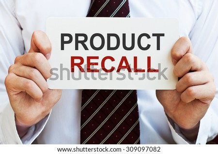 Product Recall. Man holding a card with a message text written on it - stock photo