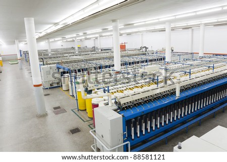 production hall of a spinning a weaving machines in a textile mill, textile factory, yarn manufacturing - stock photo