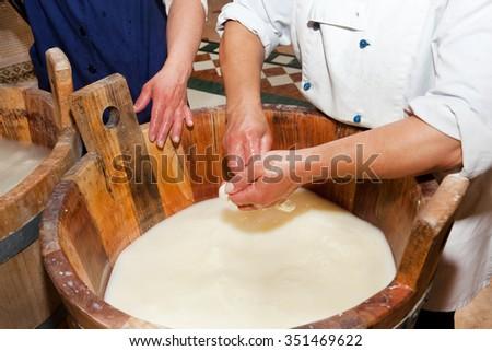 Production handmade craftsmanship of mozzarella made with Bufala milk in the Campania region in Italy. - stock photo