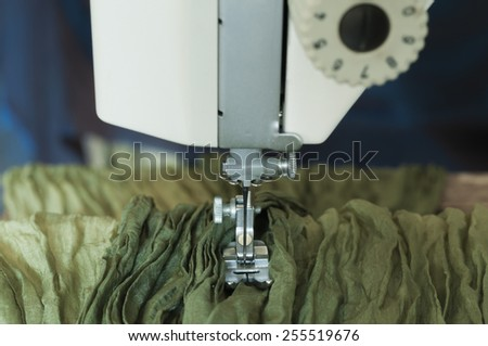 Production of garment with a sewing machine. - stock photo