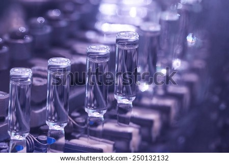 production of medicines in ampoules on automatic lines - stock photo