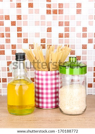 Products for cooking in kitchen on table on mosaic tiles background - stock photo