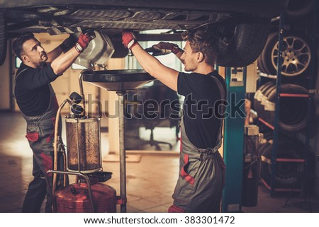 Profecional car  mechanic changing motor oil in automobile engine at maintenance repair service station in a car workshop. - stock photo