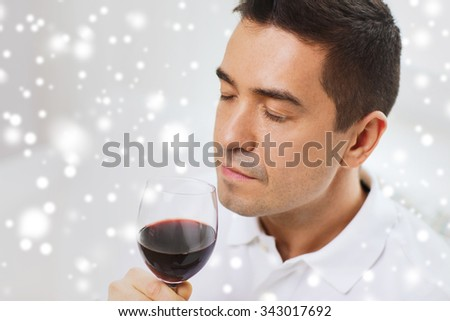profession, drinks, leisure and people concept - happy man drinking and smelling red wine from glass over snow effect - stock photo