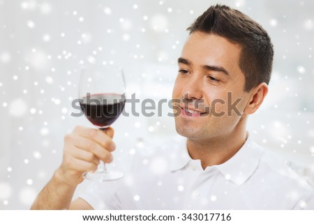 profession, drinks, leisure, holidays and people concept - happy man drinking red wine from glass over snow effect - stock photo