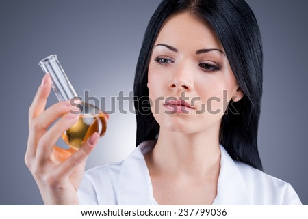 Profession of pharmacist. Female doctor in white uniform holding flask while standing against grey background - stock photo