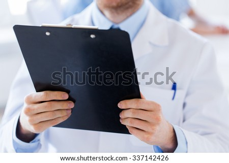 profession, people, health care and medicine concept - close up of male doctor with clipboard at hospital - stock photo