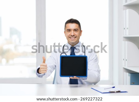 profession, people, technology, advertisement and medicine concept - smiling male doctor in white coat showing thumbs up gesture and tablet pc computer blank screen in medical office - stock photo