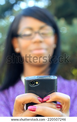 Professional African American Business Woman With Black Hair Outside Natural Pose Glasses Texting On the Phone  - stock photo