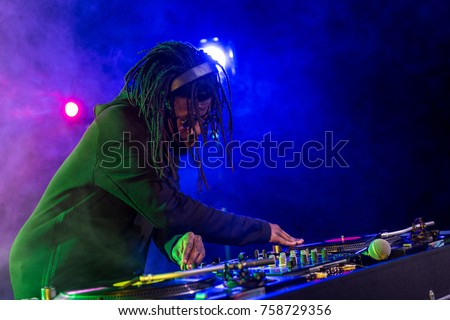 professional african american DJ in headphones with sound mixer in nightclub